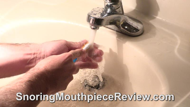 cleaning somnodent with toothbrush